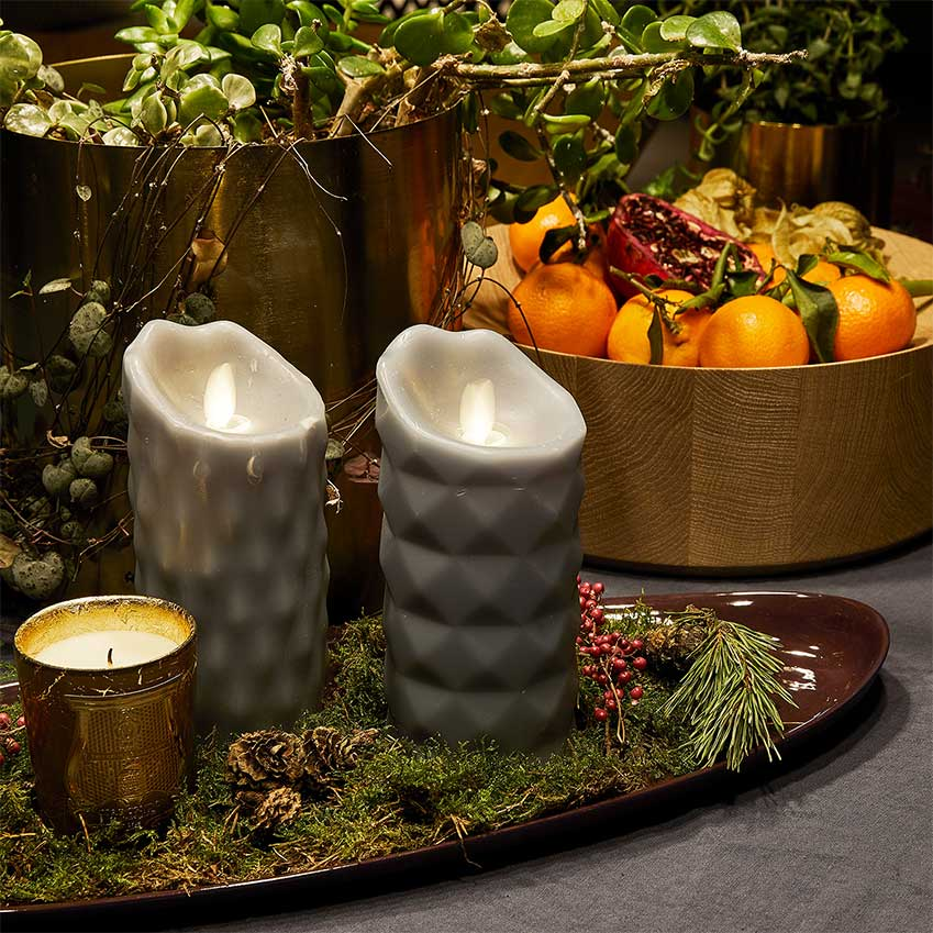 For a festive dining table, make a colourful centrepiece using fresh fruit and greenery. And don't forget the candles: living lights. Details: LED candles from Broste Copenhagen. Gold candle by Cire Trudon. Fish platter, Mud Australia.