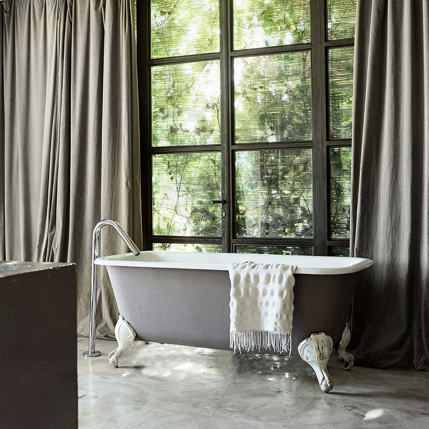 Luxurious grey drapes, a cast iron bath and concrete floors combine for sublime in this Italian house. First featured in the November 2016 edition.