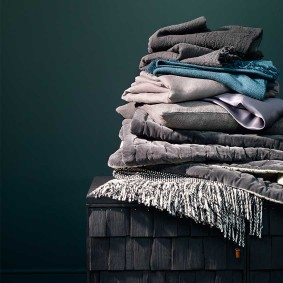 From top 'Charcoal' merino wool throw, £174, Larusi (larusi.com). 'Khullu' blue scarf, £264, Caravane (caravane.fr). Duvet cover in Light  Grey, £79.99 for a set including pillowcases, H&M (hm.com). Silk duvet cover in Silver Grey, £299, Gingerlily (gingerlily.co.uk). Cushion  cover, £29, West Elm (westelm.com). Velvet quilt in Slate by Niki Jones, £195, The Conran Shop (conranshop.co.uk). 'Tweed Emphasize'  linen blanket by Mourne Textiles, £195; 'Scorched Shake' sideboard by Sebastian Cox for Benchmark Furniture, £4,600, both The New  Craftsmen (thenewcraftsmen.com). 'Squid Ink' paint (on wall), £42.50 for 2.5 litres, Paint & Paper Library (paintandpaperlibrary.com)