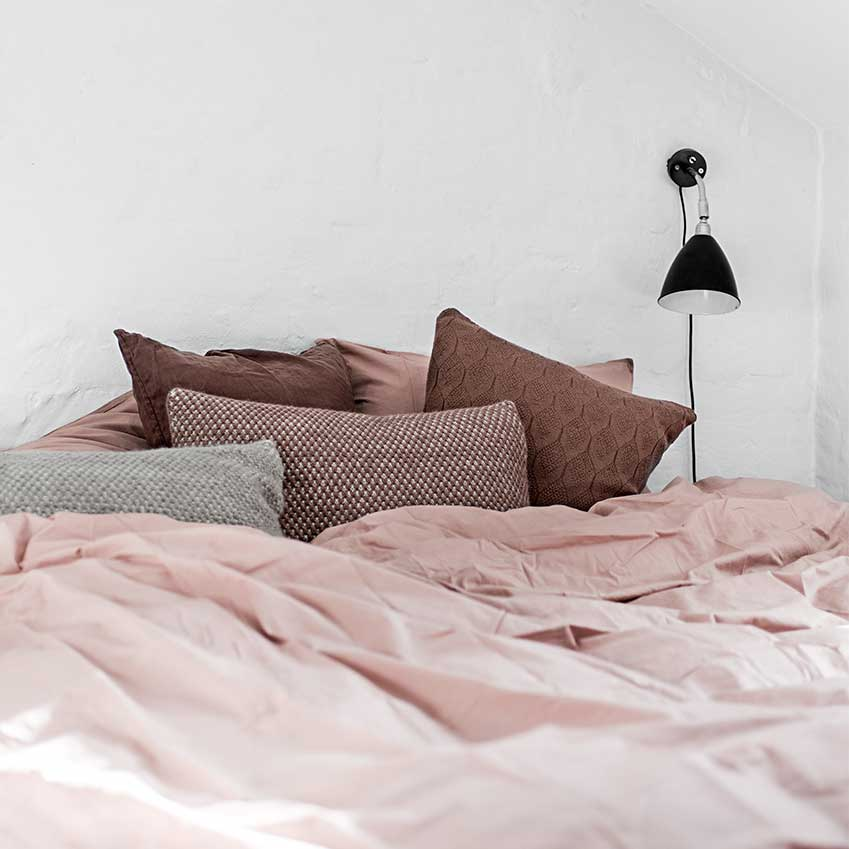 Adding a touch of spice can be as easy as adding a few pillows: From left Pink pillowcases, £42 each; duvet cover, £259; 'Heather' cushions (pictured in Grey and Velvet), £178 each; 'Raul' cushions (two pictured), £106 each, all Aiayu (aiayu.com)
