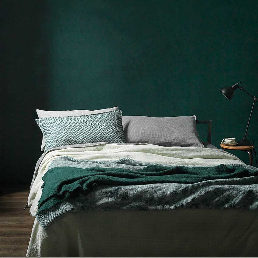 "Luxe linens from Italian bedware supremos Society Limonta, perfectly offset by a wall of green Benjamin Moore's ""Deep Sea Green"" is a good match."