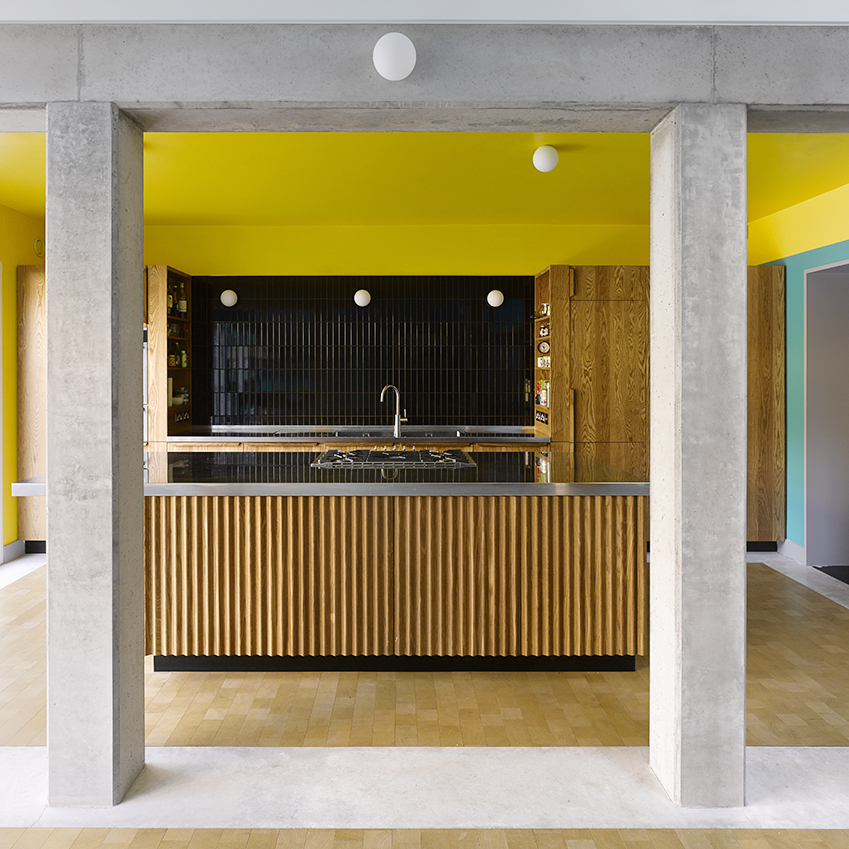 This London house kitchen designed by David Kohn Architects was painted in sunny yellow, creating a bold warming statement against the aqua walls and smoked Oak units