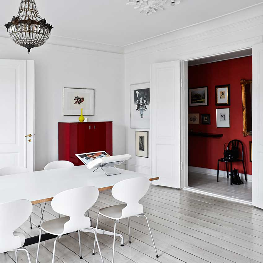 A clean, chic, typically Danish home is enlivened by painting a narrow hallway in a deliciously, deep cochineal red, and using it to display the homeowner's artworks. The colour is then echoed in the main space, which is all white, by a single red-lacquered Habitat cabinet. First featured in the June 2016 edition. Photographer Birgitta Wolfgang.