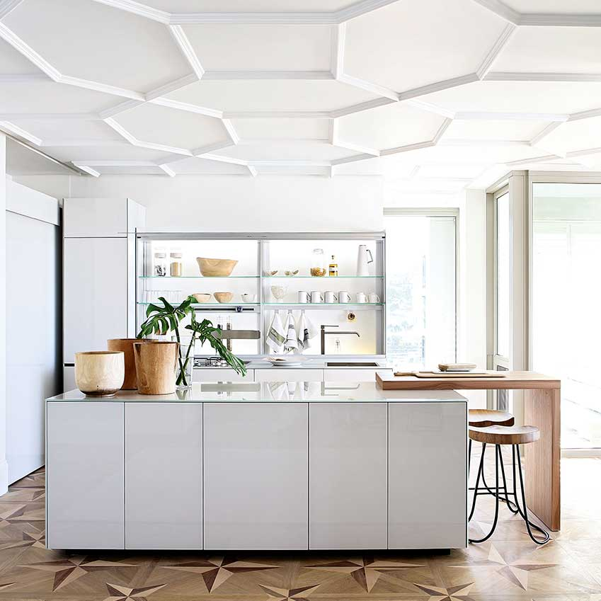 """Designed by interior designer Michele Throssell, this Cape Town kitchen features an """"Artematica"""" kitchen by Valcucine. Straight-forward and boxy with handleless cupboards, it's elevated into luxe by open glass display shelves and an intricate hand-carved wooden marquetry floor."""