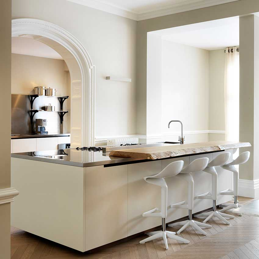 "Designed by Numero 5 Interiors, this London kitchen features a stainless-steel worktop with lacquered white Poliform units and a bespoke solid wood bar feature. The stools are the ""Spoon"" stools by Antonio Citterio for Kartell."