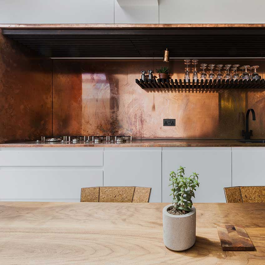 For this flat in Hackney, architecture firm Studio 304 installed clever cabinetry with integrated appliances and an alcove clad in copper, which offers drama and durability.