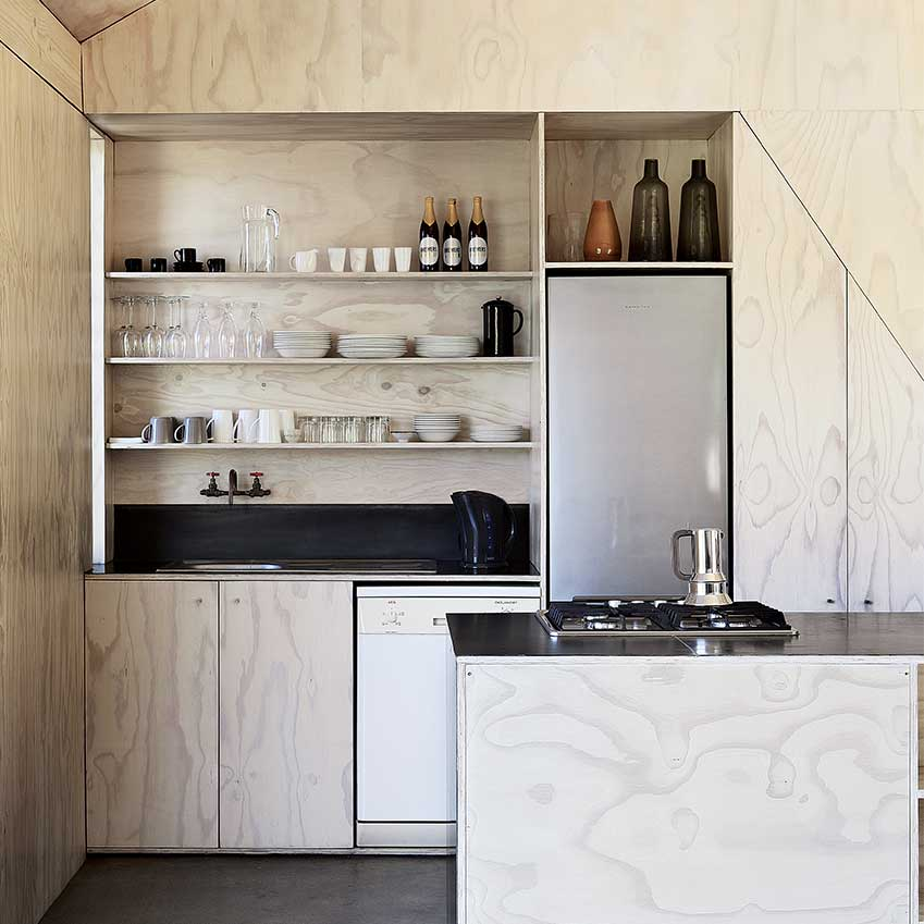 This plywood island unit and shelves were made by Beatty Vermeiren Architects for a house in South Africa.