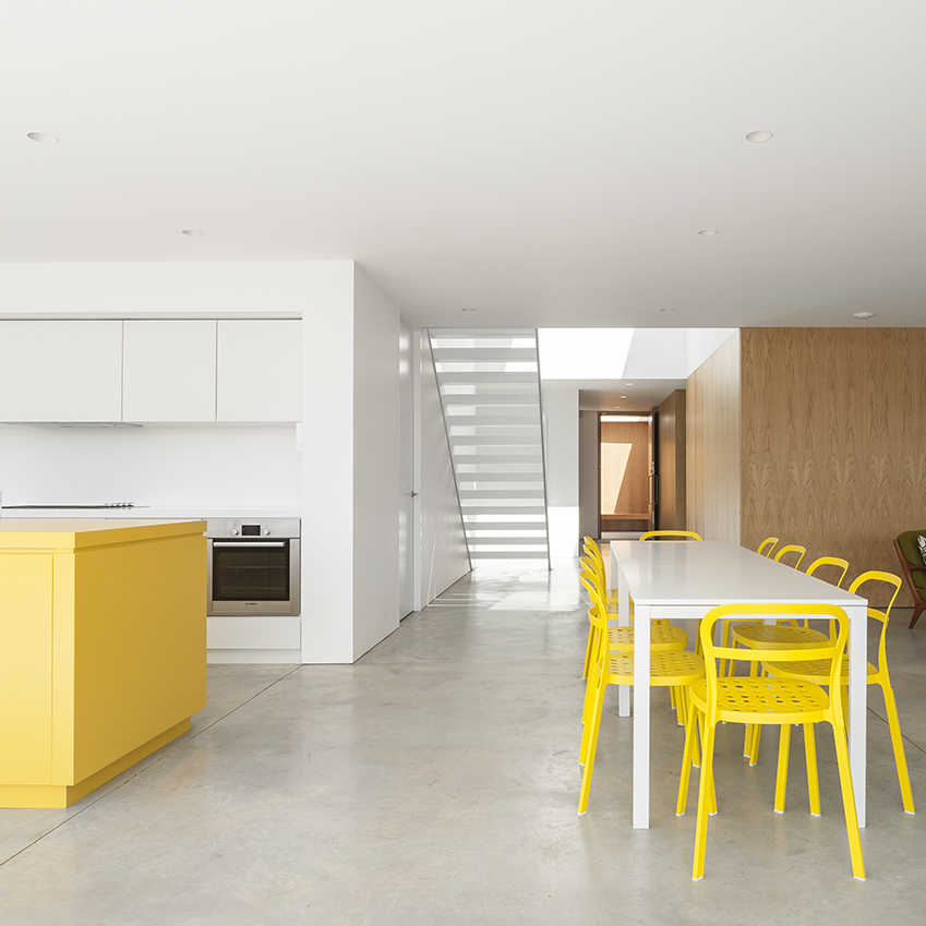 A vivid yellow kitchen (and coordinating dining chairs) is a welcome surprise in this Suffolk house designed by Soup Architects.