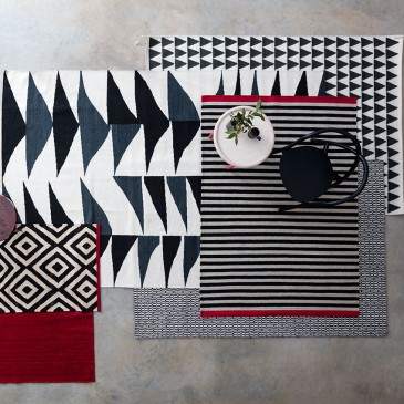 Klims: from left: small Diamond-patterned iilim, £7355, Sybilla for Nanimarquina; large 'Triangles' kilim, £795, The Conran Shop; 'Mini Flag' rug in background, top, Thomas Sandel from Asplund, £327, Twentytwentyone; Grey and black striped rug, by Lisbet Fris, £349, Fabula Living; 'Tile' be and white rug by Linnie Design, £240, Heal's.