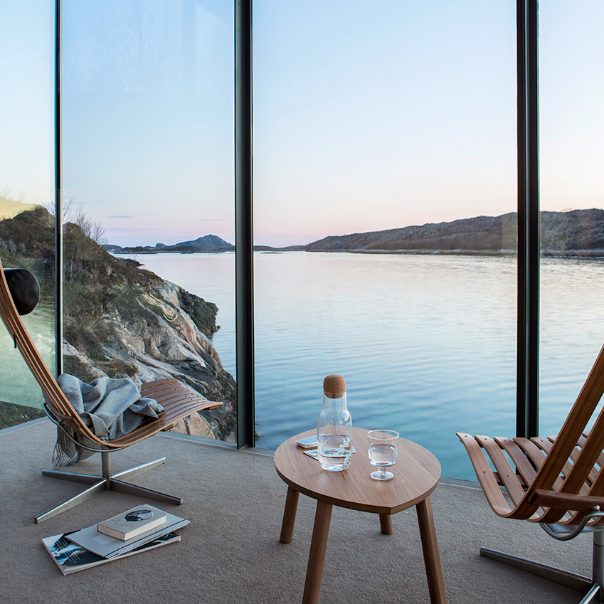 A pair of 'Scandia Senior' chairs from the Norwegian design studio Fjord Fiesta look out across the Grøtøya Strait, north of Norway. An idyllic spot if ever there was one. Home first featured in the July 2017 'wellbeing' edition of ELLE Decoration. Photography: Nadia Norskott/House of Pictures. Styling: Kirsten Visdall.