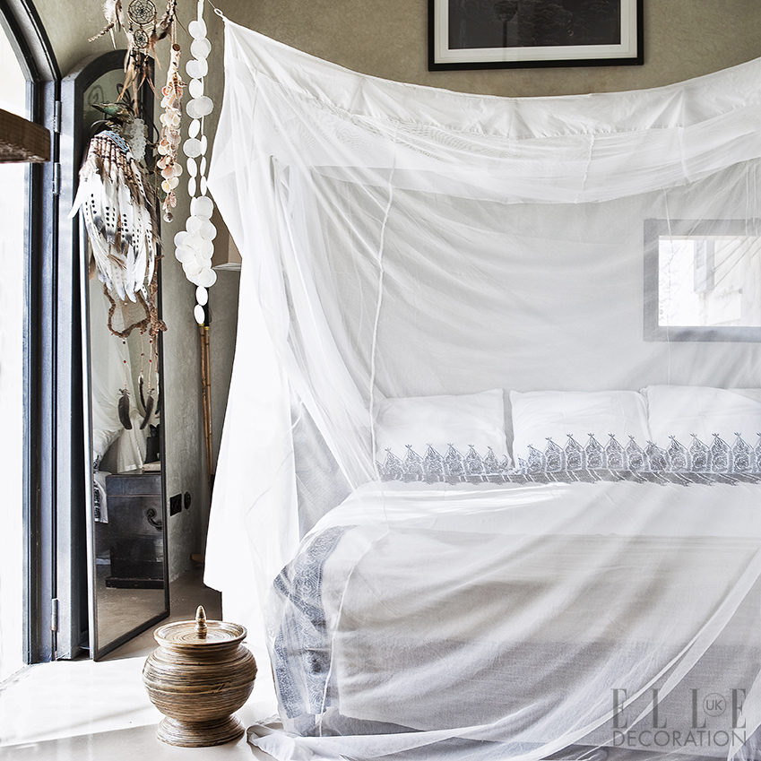 A mosquito net, draped artistically over the bed, is paired with cascading chains of shells and a feathered dream catcher, all set against the tadelakt plaster walls of this Majorcan villa<span>Photography/Production: Sunna & Marc van Praag