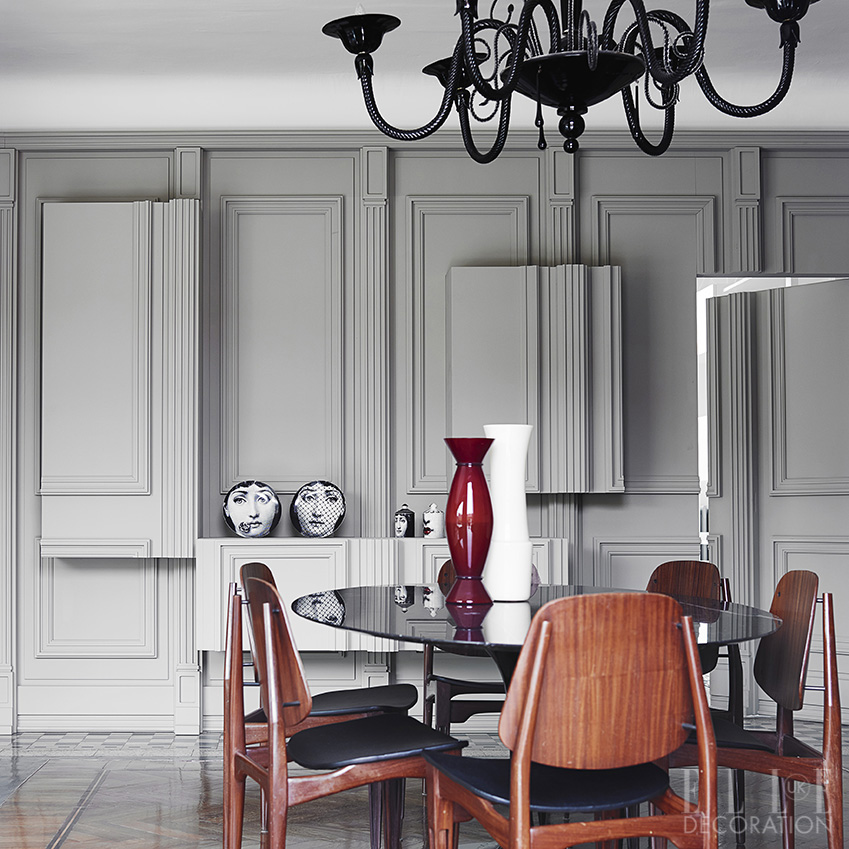 The three-dimensional panelled walls of this dining room – owned by Italian fashion designer Alessandro Dell'Acqua – conceal storage, allowing this 'Tulip' table by Eero Saarinen for Knoll (knoll.com) to take centre stage. The chairs are vintage and the chandelier is made from Murano glass<span>Photography: Fabrizio Cicconi/Living Inside  Styling: Francesca Davoli</span>