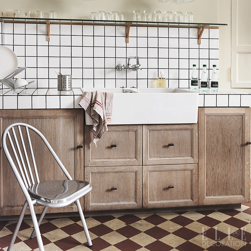 Simple wooden cabinetry teamed with a chequered floor creates a classic French-country style in this kitchen. This double Belfast sink creates a practical prep area and is flanked by simple white tiles <span>Photography: Michael Paul/Living Inside</span>