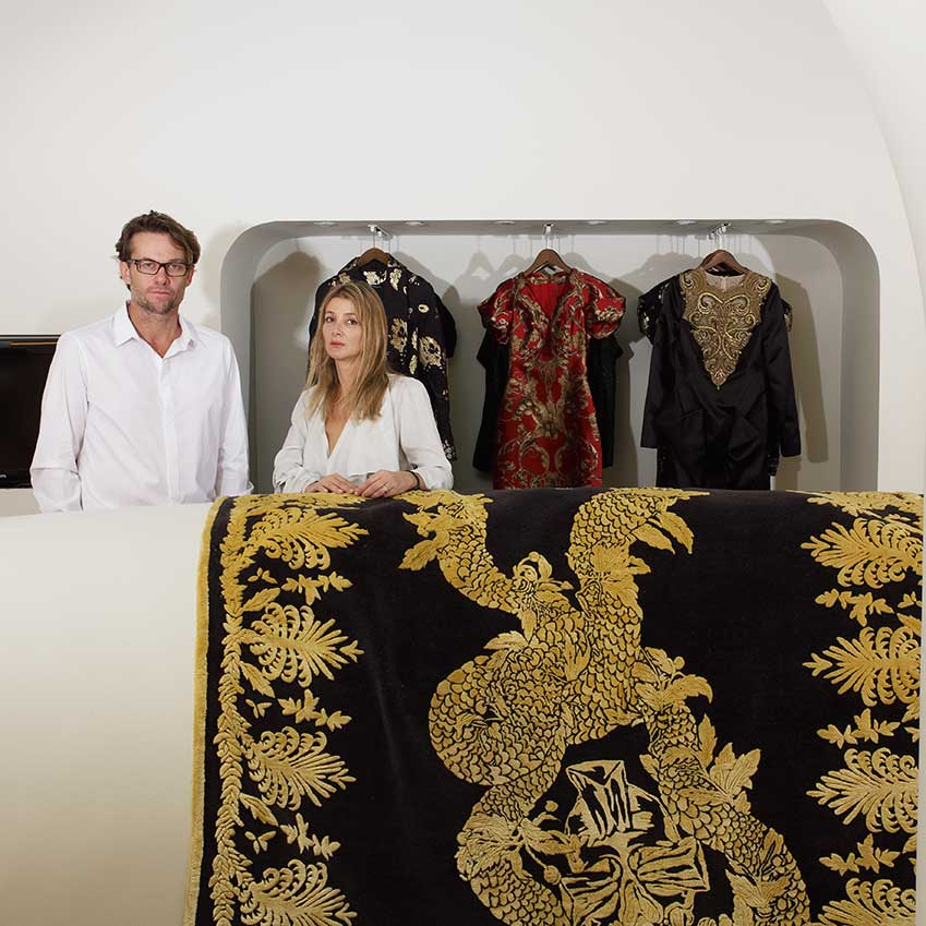 BEST FASHION CONTRIBUTION TO DESIGN: ALEXANDER MCQUEEN FOR THE RUG COMPANY – Whether it's an opulent flock of hummingbirds or the famous skull motif, all of the rugs in this collection and cushions use the finest techniques and yarns. Pictured are company founders Christopher and Suzanne Sharp with McQueen's 'Military Brocade' design (therugcompany.info)