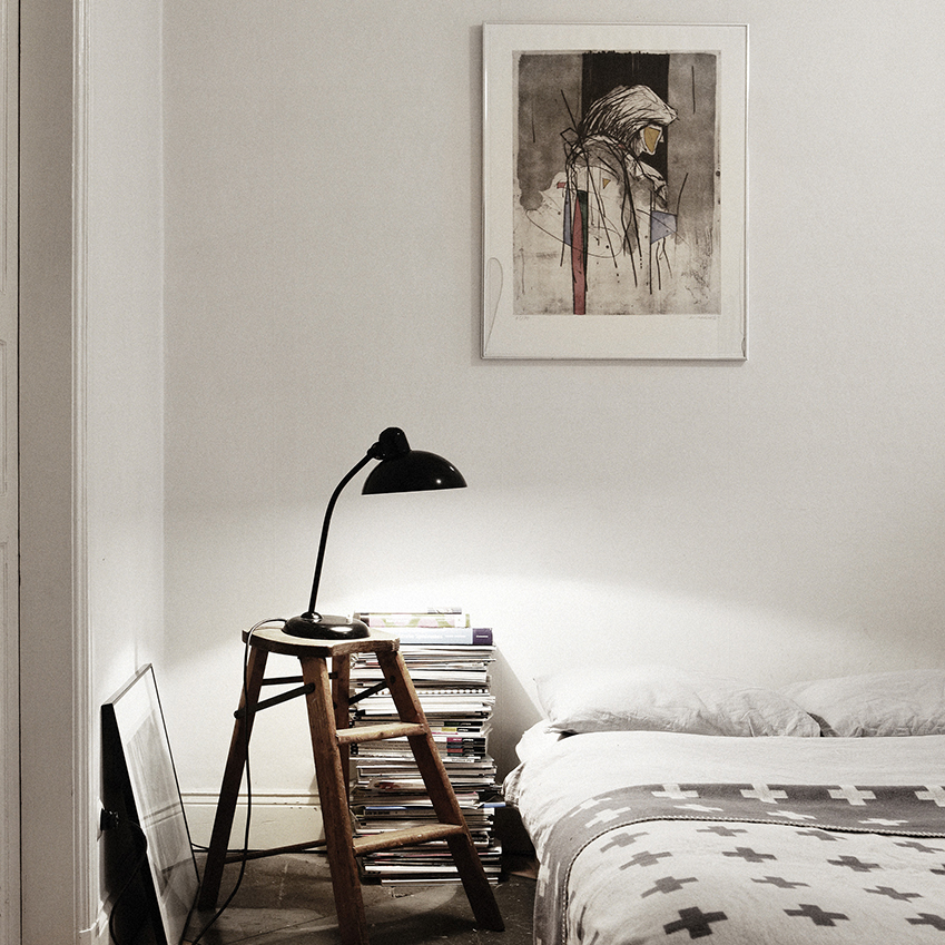 A black lamp and graphic patterned bed sheets contribute to the monochrome scheme in this simple bedroom