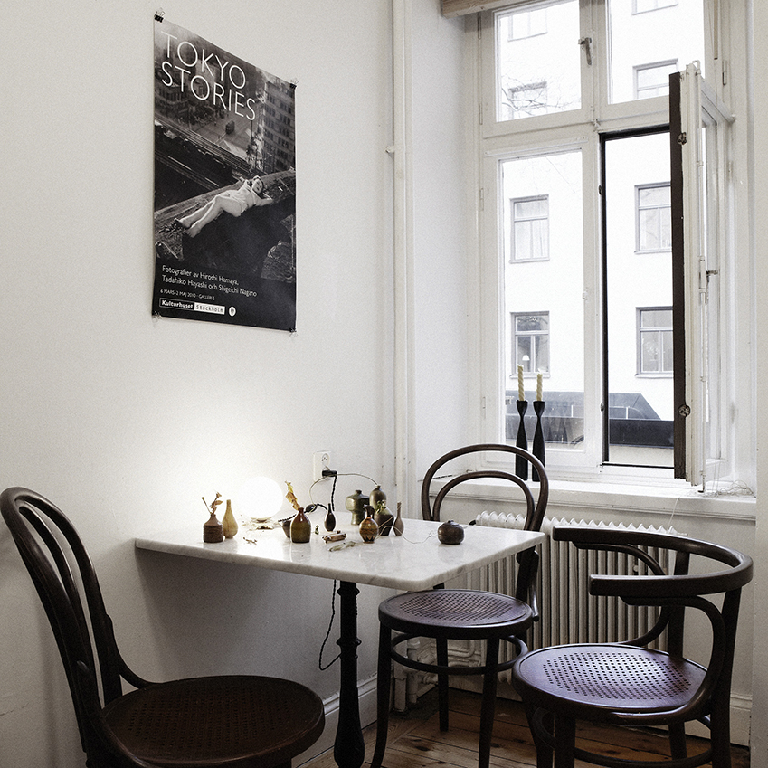 A black-and-white poster stands out against the plain walls in this dining area