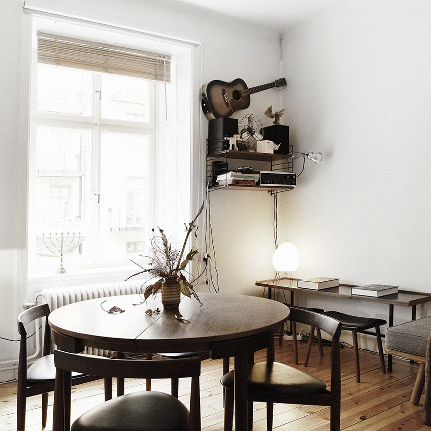 Dark furniture sits in contrast with the lighter walls and floors in this dining area