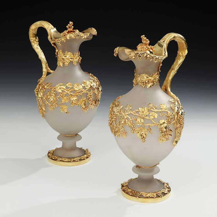 A decorative pair of frosted glass claret jugs (1840), manufactured by Mortimer and Hunt and exhibited by J H Bourdon-Smith Ltd