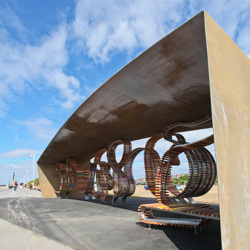 Image 1 of 8: The Longest Bench stretches along Littlehampton's promenade and can seat up to 300 people. Designed by Studio Weave, the bench twists and turns along the boardwalk and incorporates bronze-finished shelters