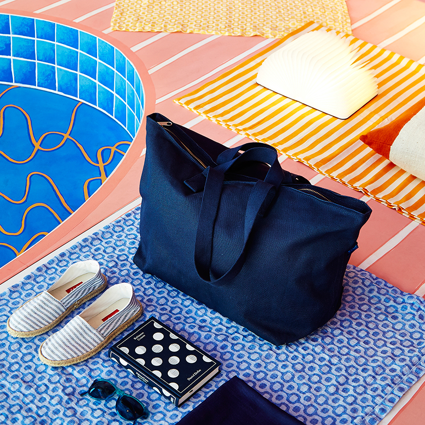 'Baggu' Weekend bag, £69; 'Resort' shoes, £85; 'Lumio' book lamp, £195; 'Robinson Crusoe' book, £14.99; linen beach towel, £120; striped beach towel, £120; 'Kauai' Sunglasses by Sunpocket, £75, all The Conran Shop